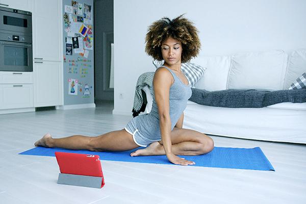Young woman practicing yoga watching tutoria